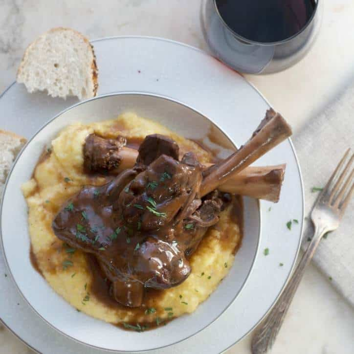 A photo of the final dish served over polenta from above Lamb Shanks in Wine Sauce