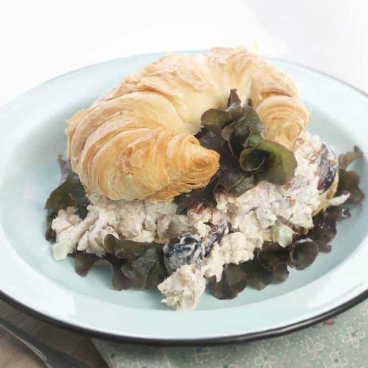An image of How to Make Southern Style Chicken Salad with Rotisserie Chicken on a croissant with the chicken salad falling out the sides and lettuce poking out under the chicken salad