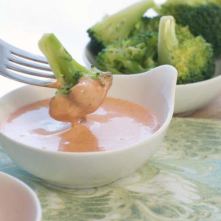 Shrimp Sauce Yum Yum Sauce with Broccoli being dipped in. Broccoli in background.