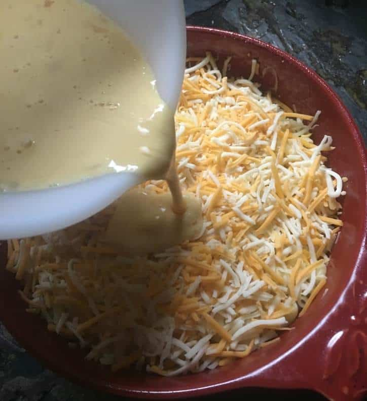 A photo of the mixture being poured over the noodles and cheese for easy baked macaroni and cheese
