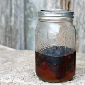 A photo of blackberries in the pickling liquid in a Mason Jar
