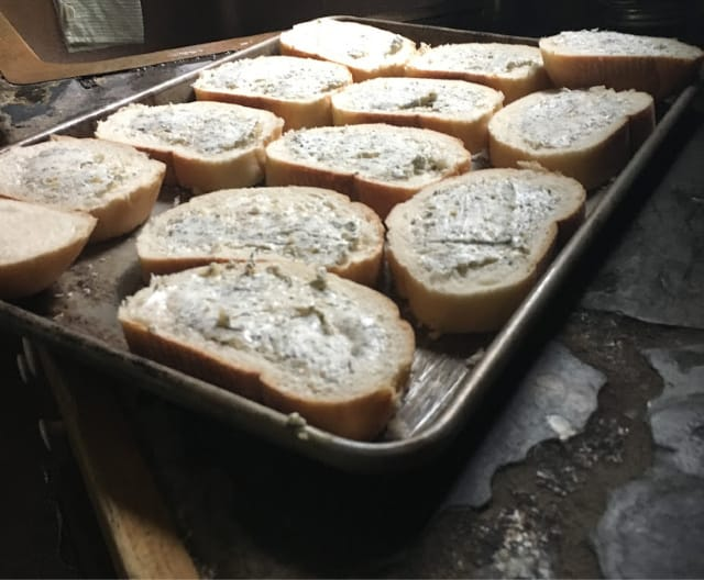 Herbed butter spread on the bread and placed in baking sheet