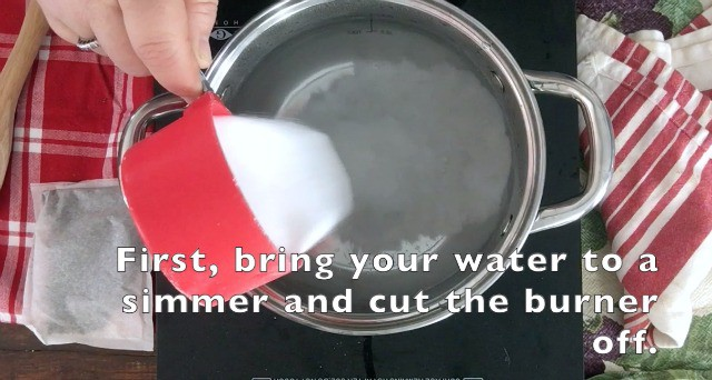 1 cup of sugar being added to hot water in sauce pan