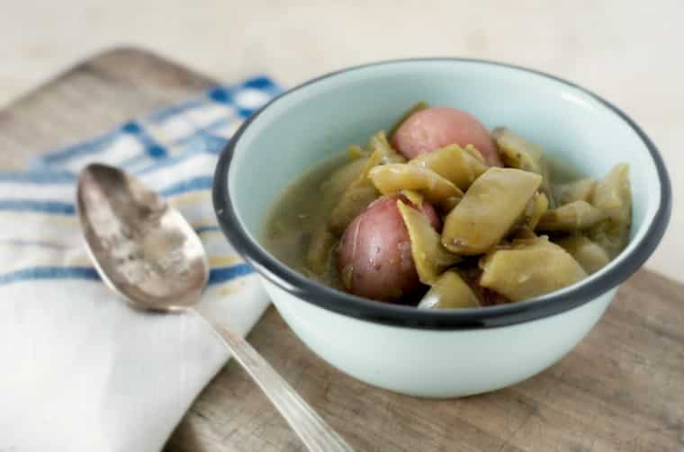 green beans and new potatoes in a blue bowl with napkin and spoon