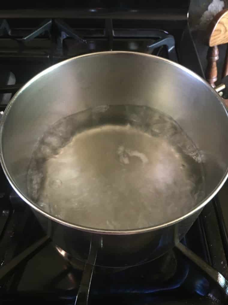 A photo of boiling water in a silver sauce pan