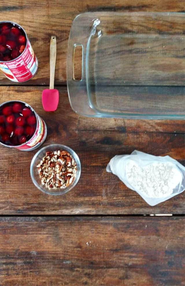 BAKING DISH, PECANS, CANNED CHERRIES CAKE MIX AND A SPATULAT