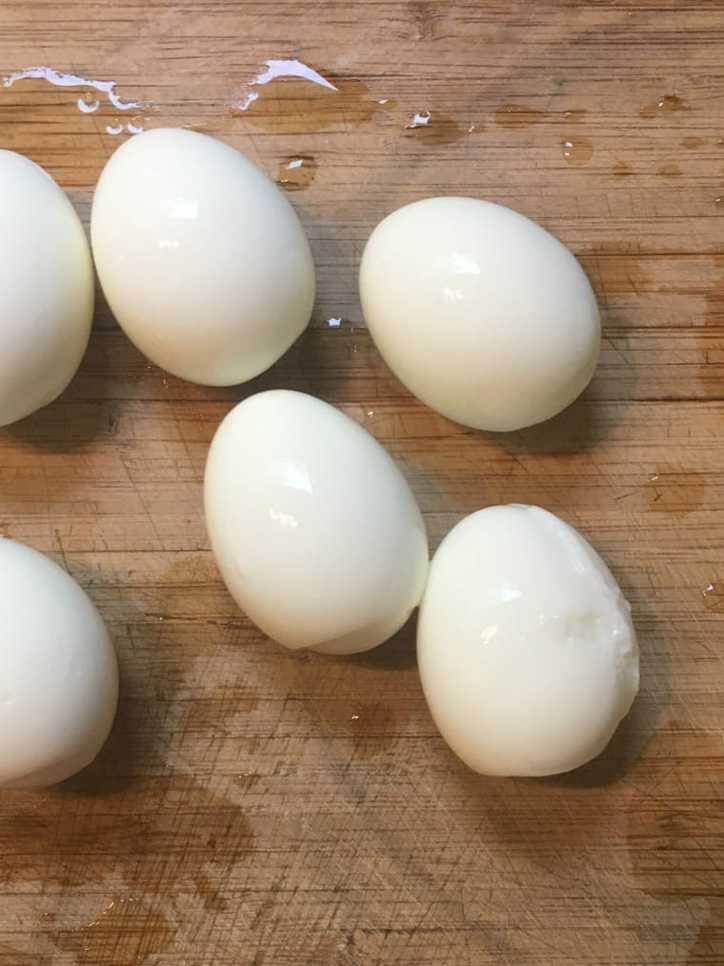 A photo of six boiled Eggs on cutting board.