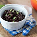A close up photo of how to cook canned black beans on the stove