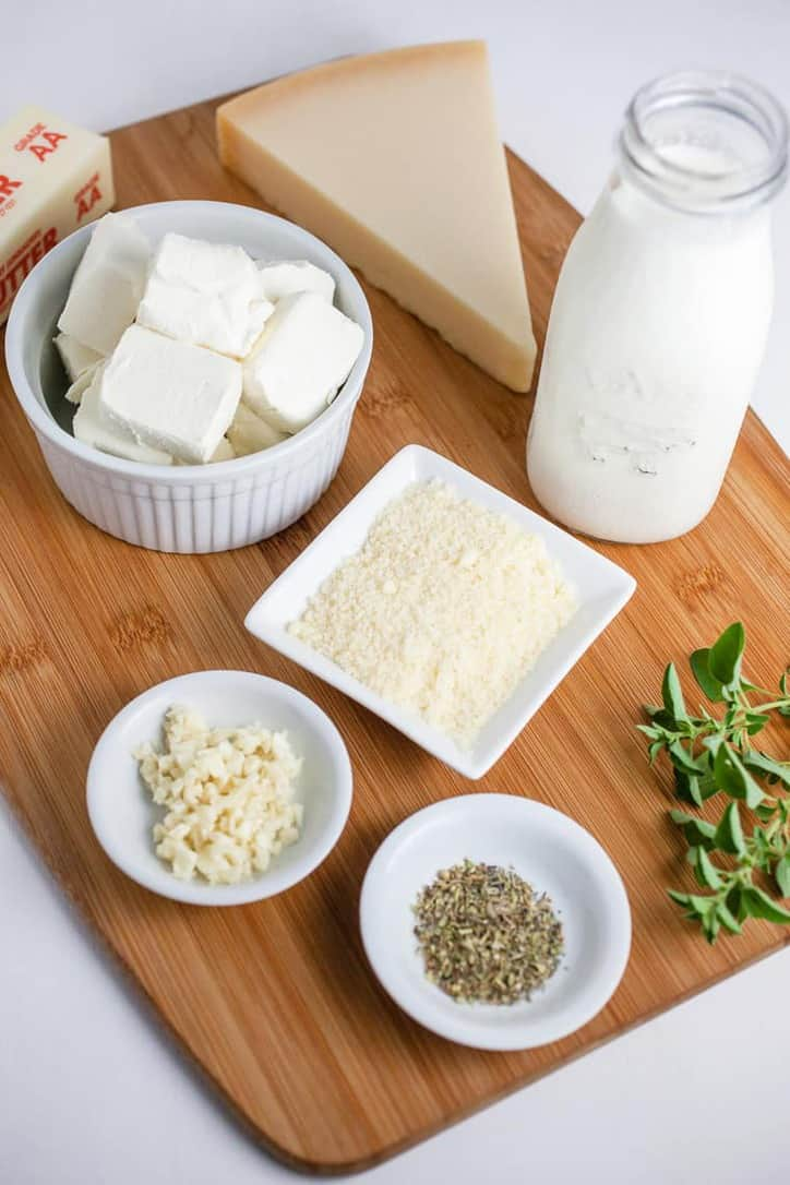 a cutting board with bowls of cream cheese, parmesan, garlic, dried oregano a bottle of milk and a block of parmesan