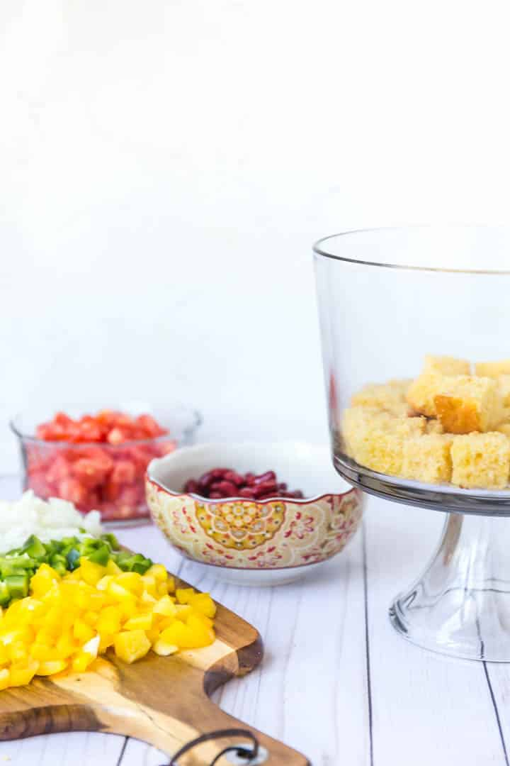 A photo of a glass trifle bowl with cornbread in the bottom, cutting board of ingredients.