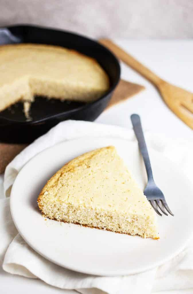 A slice of Southern Cornbread with iron skillet in back ground