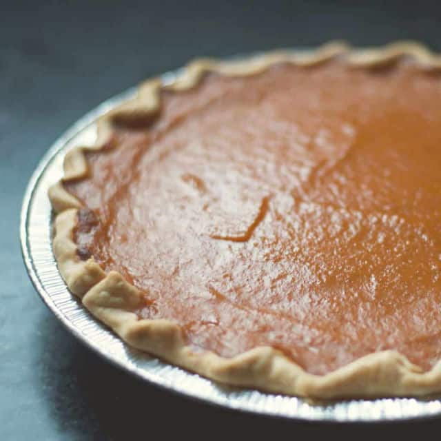 pumpkin pie from the side in an aluminum pie pan