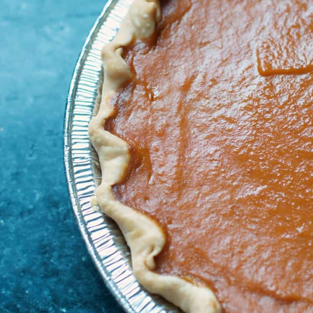 close up of the edge of a pumpkin pie on a gray table