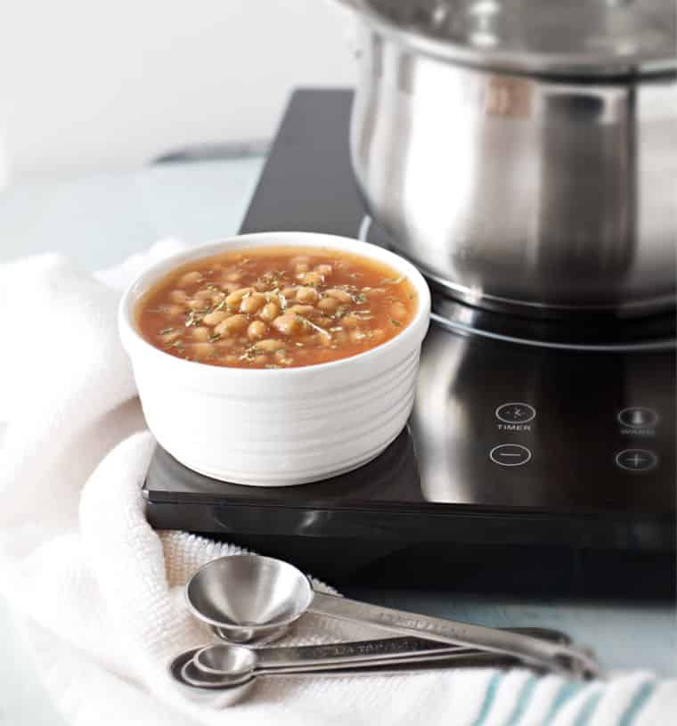 A bowl of baked beans sitting on a cooktop for How to Cook Canned Baked Beans