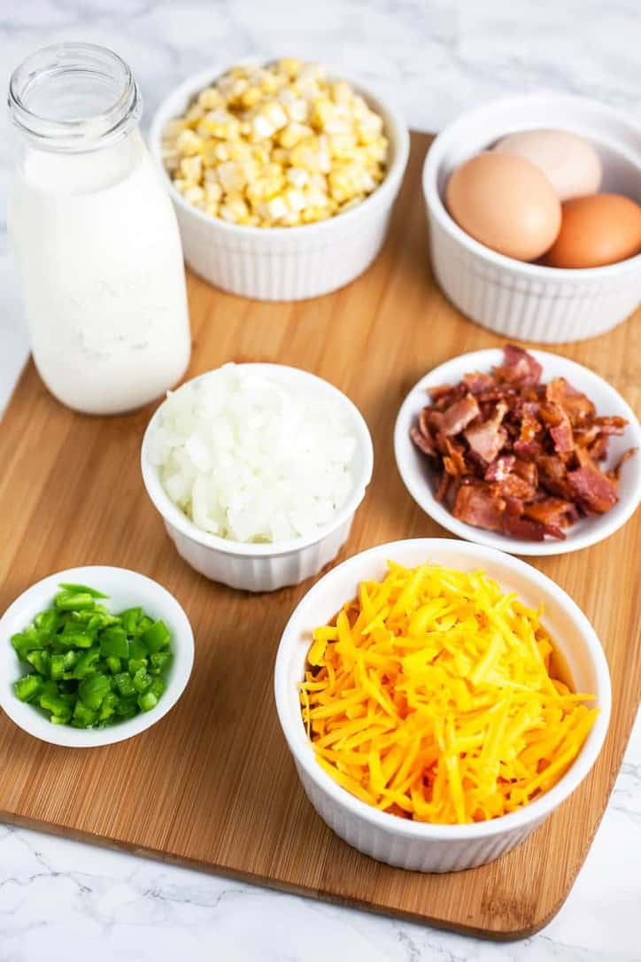 Ingredients such as cheese, bacon, eggs, onions milk and peppers in small bowls ready for a recipe