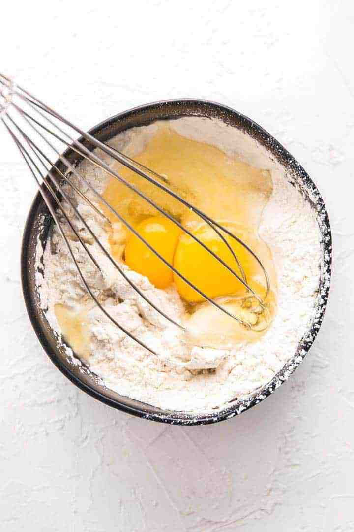 A photo of a black bowl, two eggs, flour and a whisk