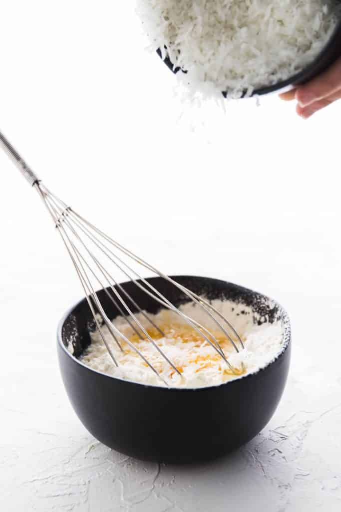 Sprinkling the coconut into the coconut custard pie filling mix