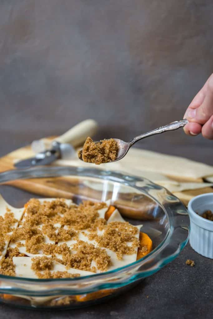 adding more ingredients to sweet potato cobbler