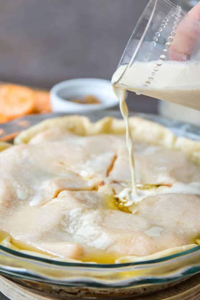Adding the evaporated milk to the sweet potato cobbler