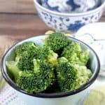 Bowl of broccoli with a patterned blue bowl in the back ground for how to cook frozen broccoli