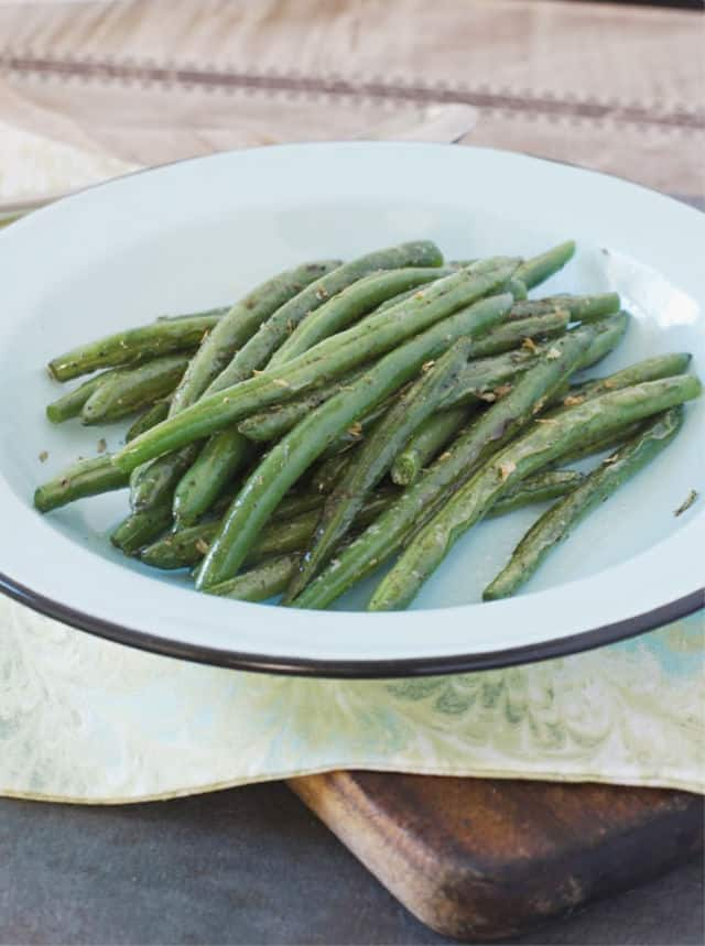 Blue plate of green beans and blue green kitchen towel for how to saute green beans