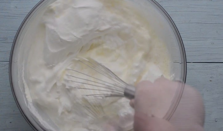 a glass bowl with cool whip, sour cream and milk and whisk