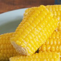 Close up photo of a glistening ear of corn sitting on other ears on a blue plate