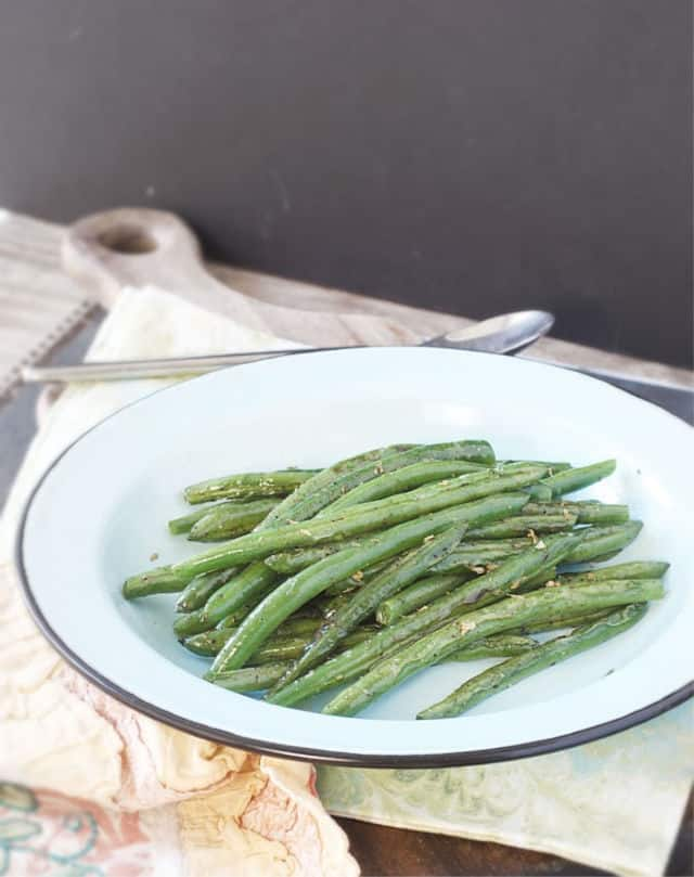 A blue plate of green beans with spoon