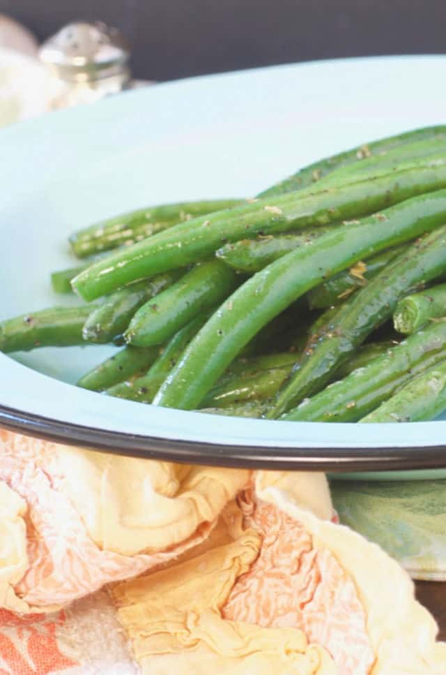 A close up of a plate of green beans sitting on an orange kitchen towel
