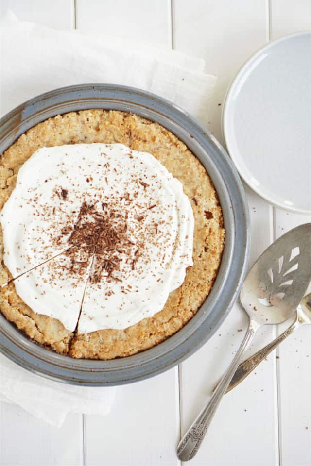 Top down look at the ritz cracker crust of this peanut pie with serving pieces in background