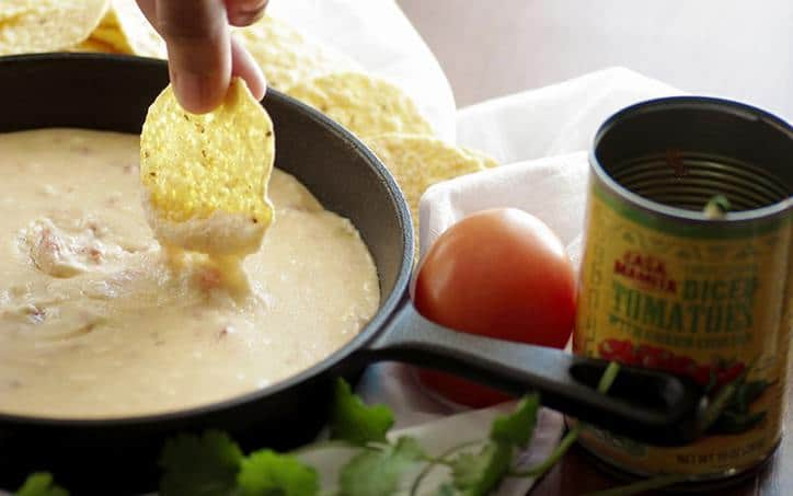 A photo of a chip dipping into the queso with cheese dripping off and a tomato