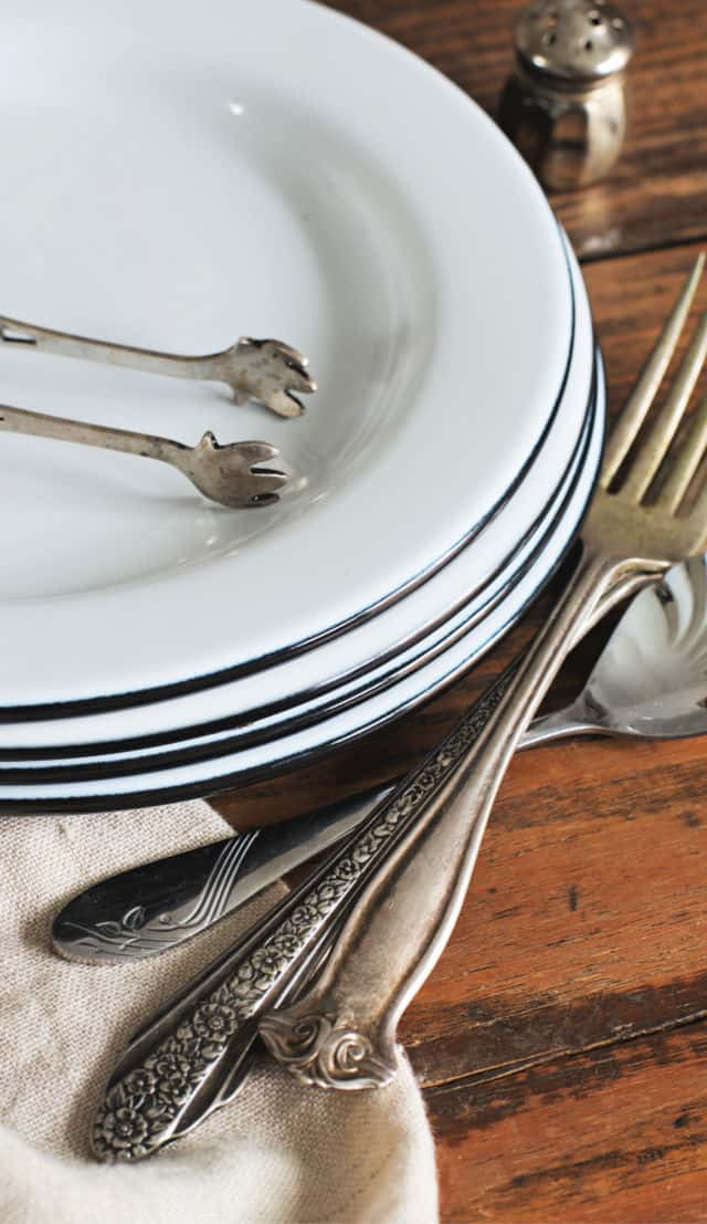 Stack of white plates with small tongs, silverware and napkin