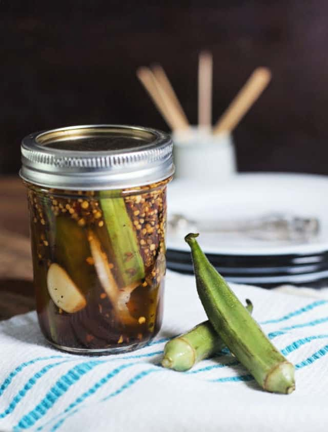 A jar of pickled okra and two okra pods sitting on a white and blue towel with plates and toothpicks in background