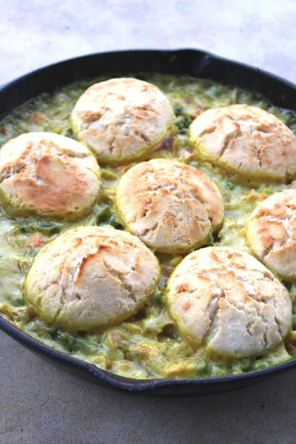 A cast iron skillet of pot pie with biscuits baked into the upper crust