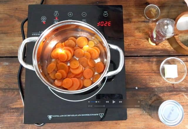 A saucepan full of canned carrots on the stovetop