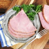 A view of three slices of ham on a grey plate with a blue napkin