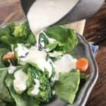 Silver bowl pouring restaurant ranch dressing onto green salad on grey plate
