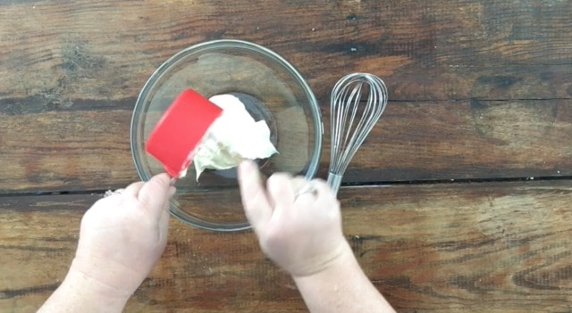 a photo of a cup measure with mayonnaise pouring into a glass bowl with a whisk to the right