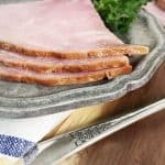The edge of three pieces of ham on a gray plate with a napkin and the handle of a fork