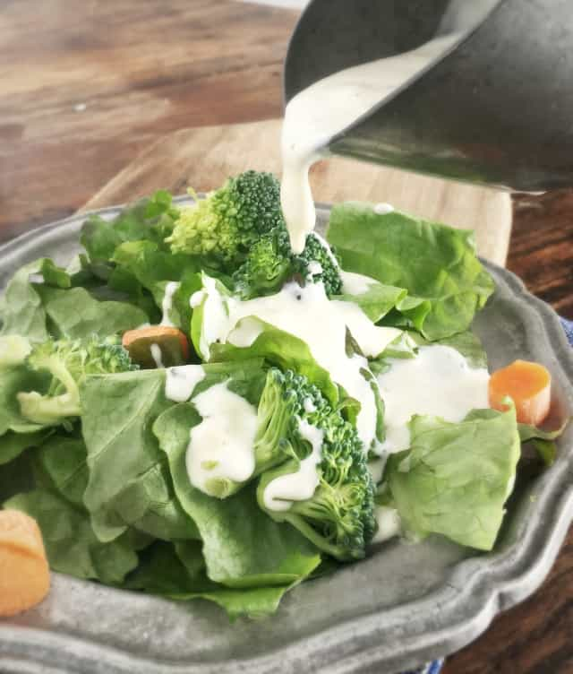 Creamy white restaurant ranch dressing pouring onto a green salad with orange carrots and green broccoli on a grey plate