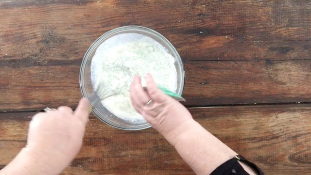 A photo of adding a ranch packet to the milk and mayonnaise mixture in a glass bowl