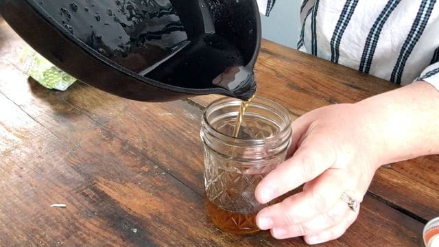 pouring the bacon grease into the jelly jar