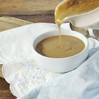 A gravy boat pouring gravy into a small white bowl sitting on a white napkin with wood table