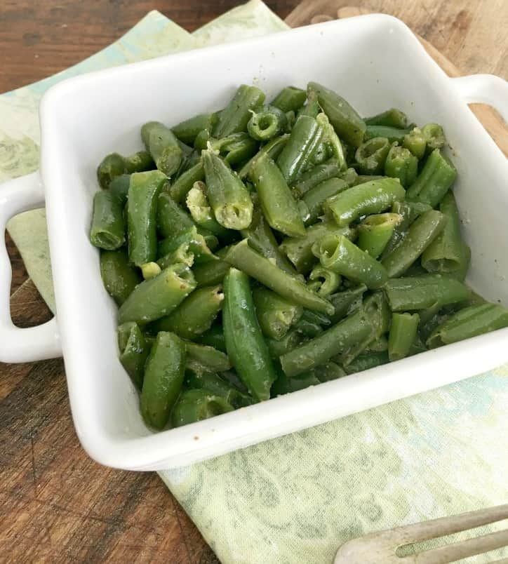 a small square white bowl holding the cooked green beans with green napkin underneath