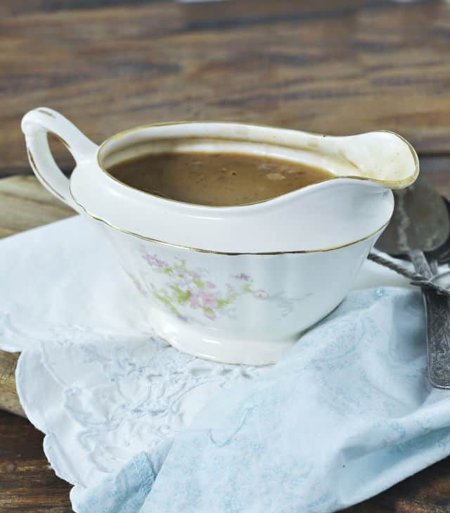a china gravy boat filled with gravy sitting on a white napkin and wood table