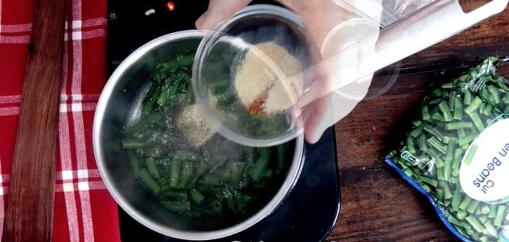 A small glass bowl adding seasonings to saucepan of green beans cooking below