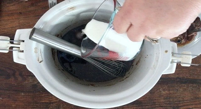 Hand pouring the glass fluid measure of cornstarch slurry into the crockpot of meat broth