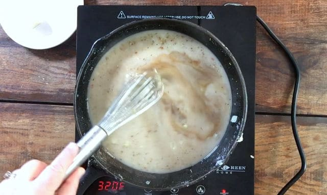 Whisking the brown liquid ingredients in the frying pan to thicken