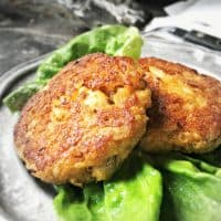 Two crab cakes on a silver plate with green lettuce.