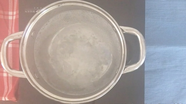 A saucepan on a cooktop with steam rising and bubbles from bottom